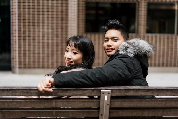 ベンチに一緒に座っているカップルの背面図