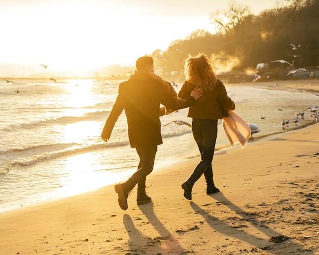 冬のビーチを歩いているカップルの背面図