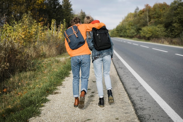 一緒に道路脇を歩いているカップルの背面図