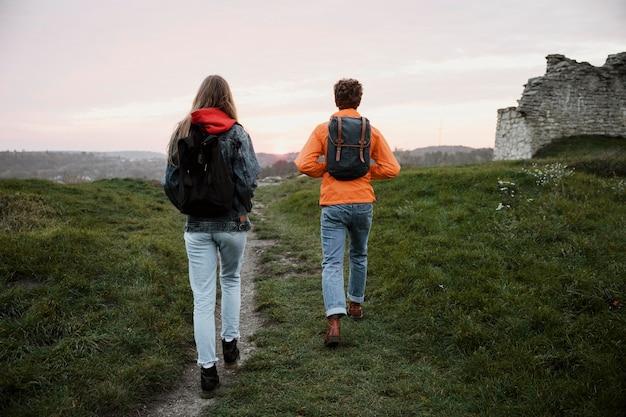 一緒にロードトリップ中に歩いているカップルの背面図