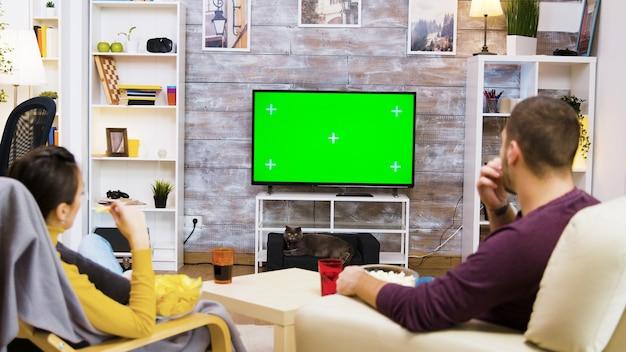 Вид сзади пара смотрит телевизор дома с зеленым экраном, ест попкорн и кот смотрит на них.