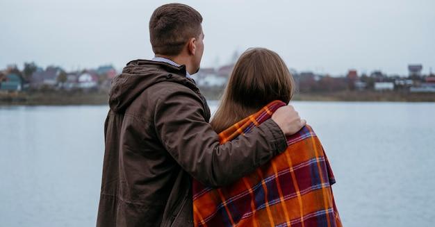 湖の景色を眺める毛布を持ったカップルの背面図
