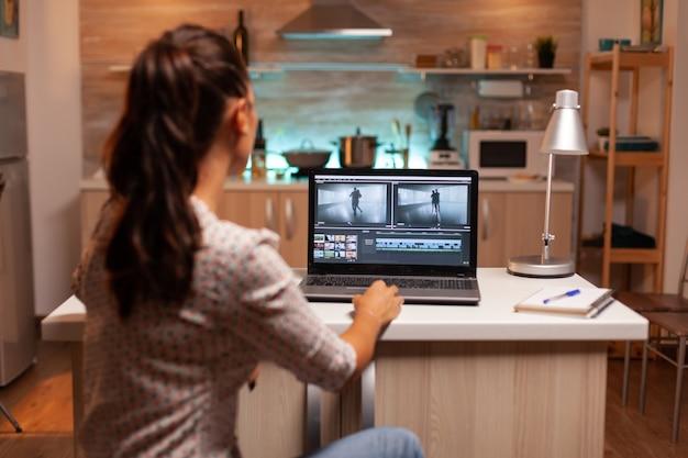 真夜中にラップトップで映画に取り組んでいる創造的な映画製作者の背面図。深夜に編集するための最新のソフトウェアを使用して映画のモンタージュに取り組んでいる在宅勤務のコンテンツ作成者。