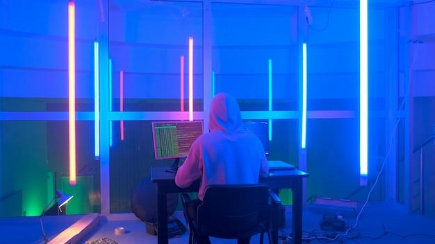 Вид сзади на преступного хакера, работающего вечером на компьютере в большом офисе с теплым неоновым светом ...