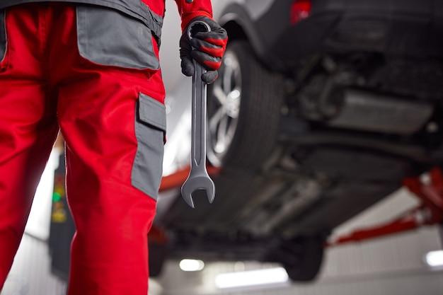 Вид сзади неузнаваемого мужчины-механика в униформе и перчатках, стоящего возле машины с гаечным ключом в руке перед процессом ремонта в гараже