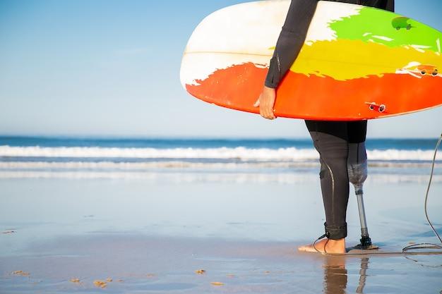 Вид сзади обрезанного мужчины-серфера, стоящего с доской для серфинга на морском пляже