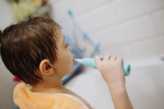 Вид сзади симпатичного 67-летнего мальчика с полотенцем на плечах, чистящего зубы электрической щеткой
