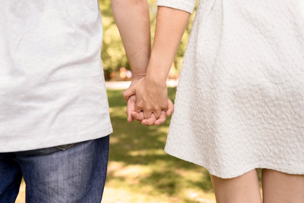 公園で手を繋いでいるかわいいカップルの背面図