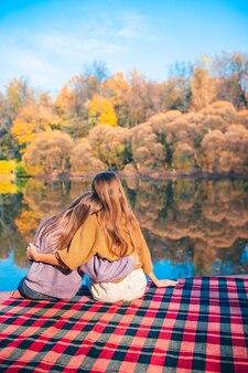 湖で秋の日を楽しんでいるかわいい女の子の背面図