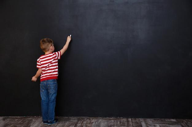 Вид сзади милый маленький мальчик, пишущий с мелом