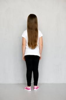 白いtシャツと黒いスウェットパンツのポーズで長い髪のかわいい若い子の背面図