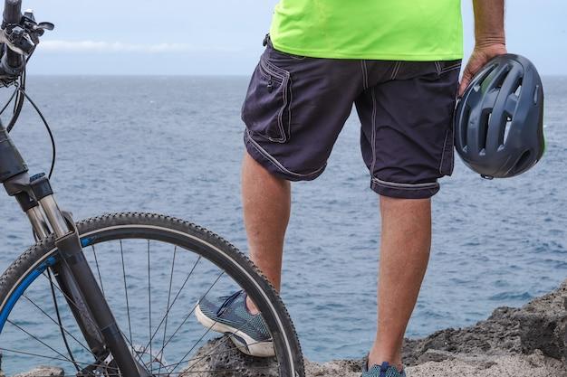 전기 자전거로 활동한 후 절벽에서 바다에서 쉬고 있는 자전거 타는 남자의 뒷모습. 헬멧을 손에 들고 서서