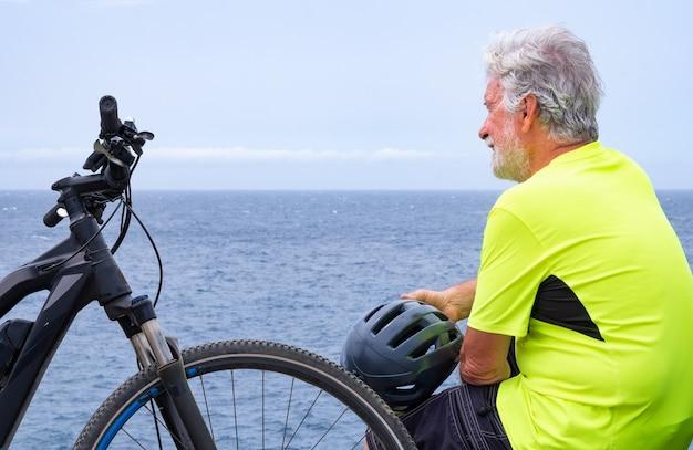 Вид сзади велосипедиста, отдыхающего в море на скале после активности со своим электровелосипедом. стоя со шлемом в руке