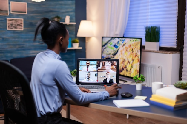 浅黒い肌の女性の背面図は、ビデオ通話の過程で多様な同僚と話します。残業をしている仮想会議で話す最新のテクノロジーネットワークワイヤレスを使用します。