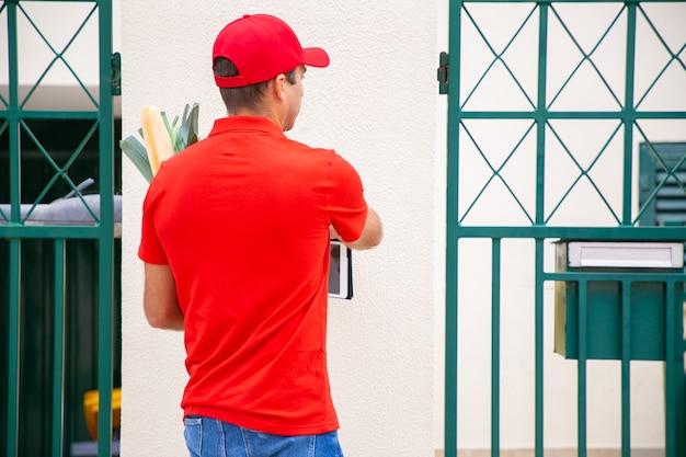 ドアベルを鳴らし、タブレットを保持している配達員の背面図。野菜とパンを紙袋に入れて赤いシャツを着て配達するプロの宅配便業者。配送サービスとオンラインショッピングのコンセプト