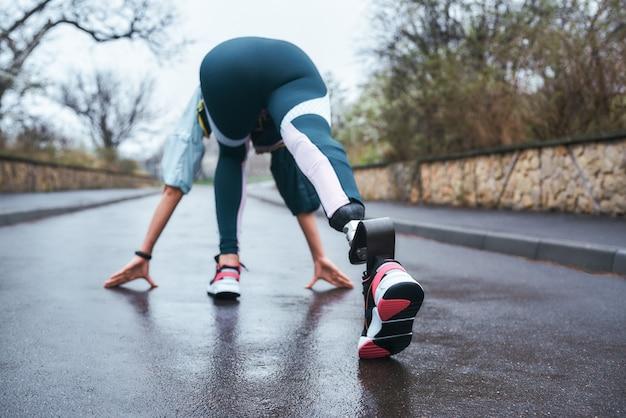 Вид сзади женщины-спортсмена-инвалида в спортивной одежде с протезом ноги, готовящейся к бегу на открытом воздухе