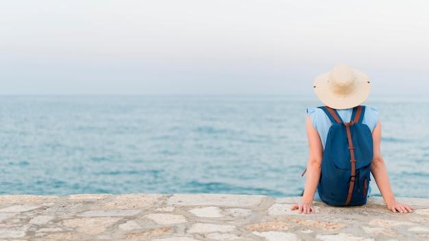 海の景色を楽しみながら年長の観光客女性の背面図