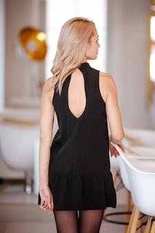 ビューティーショップインテリアでエレガントな服装の若い女性の背面図。屋内で立っているハイヒールのスリムなビジネス女性の背面図