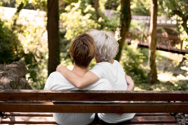 ベンチから公園の景色を眺めながら抱きしめるカップルの背面図