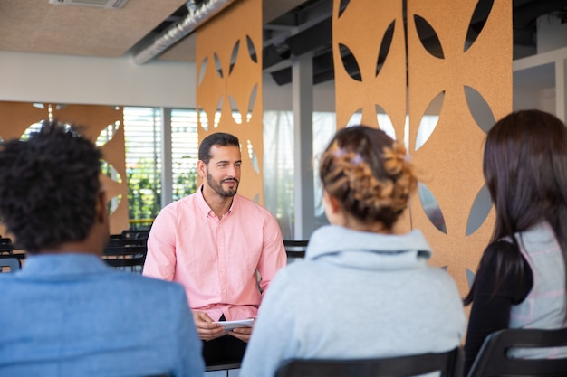 若いコンサルタントに耳を傾ける従業員の背面図