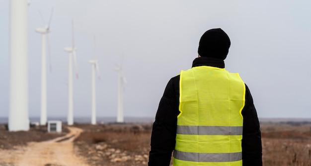 Вид сзади инженера, смотрящего на ветряные турбины в поле