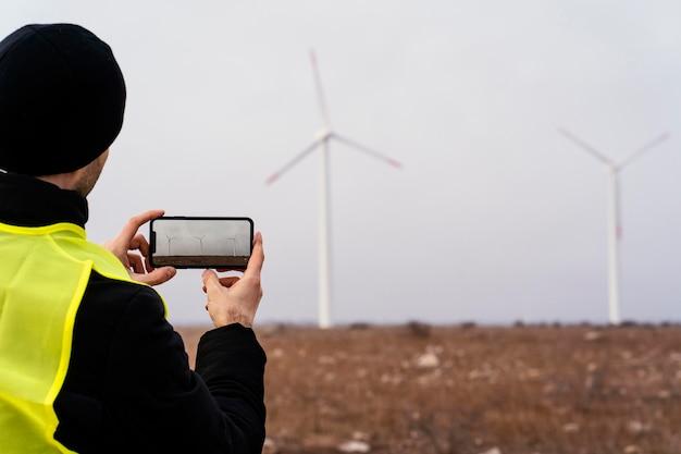 Вид сзади инженера, фотографирующего ветряные турбины в поле