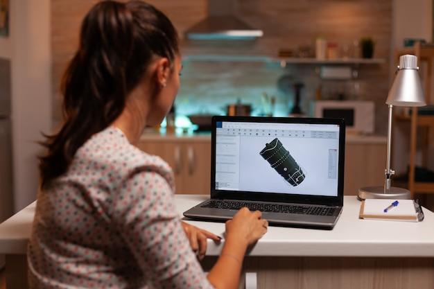 Вид сзади инженера, работающего над проектом турбины в домашнем офисе в ночное время. промышленный инженер-женщина работает на персональном компьютере, показывая программное обеспечение cad.