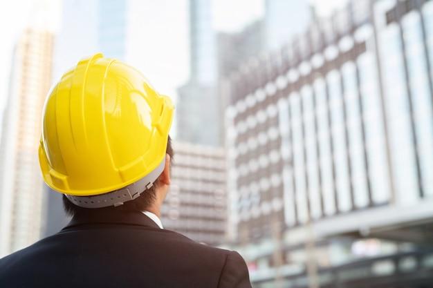 작업 작업의 안전을 위해 엔지니어링 남자 건설 노동자 정장 의류 착용 안전 헬멧의 후면보기. 엔지니어 서 찾고 프로젝트 성공. 관리자 프로젝트 사이트.