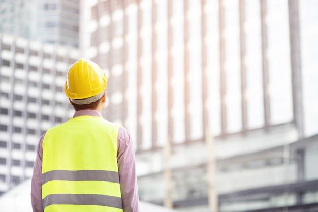 엔지니어링 남자 건설 노동자의 뒷모습은 작업 작업의 안전을 위해 안전 헬멧을 착용하고 반사 의류를 착용하십시오. 엔지니어 서 찾고 프로젝트 성공.