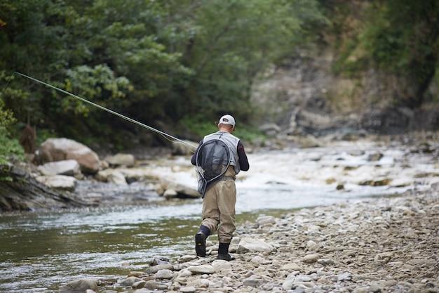 Вид сзади опытного рыбака, одетого в водонепроницаемую одежду, гуляющего по горной реке и ловящего рыбу с удочкой. понятие об активном образе жизни.