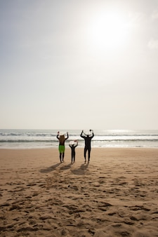 Вид сзади семьи с досками для серфинга над головой
