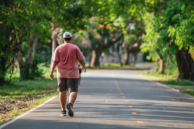 公園でジョギングや屋外で運動している太った男の背面図、健康的なライフスタイルの概念。