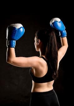 保護手袋を持つ女性のボクサーの背面図