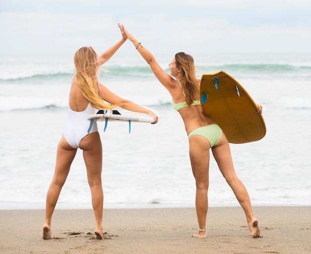 お互いにハイタッチするビーチでの女性の友人の背面図