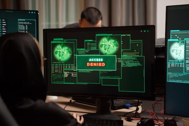 Вид сзади на женщину-хакера, которой отказано в доступе при попытке взломать брандмауэр.