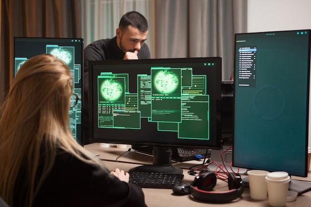 Вид сзади женского хакера, вводящего вирус на компьютере. мужской хакер в фоновом режиме.