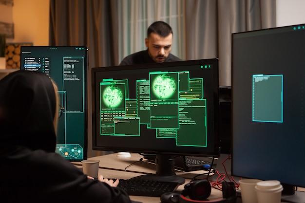 Вид сзади на женщину-хакера, пишущую вредоносное по и кибер-террориста в фоновом режиме.