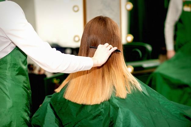 Вид сзади девушки-парикмахера, расчесывающей длинные волосы молодой блондинки клиента в салоне красоты