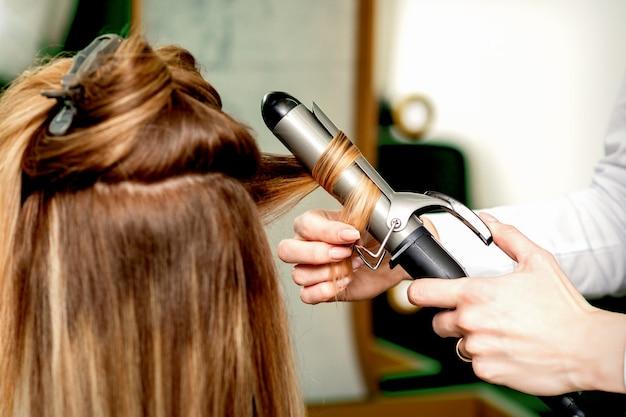美容院でヘアアイロンで女性の髪をカールする女性の美容師の手の背面図