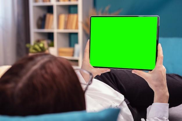 Вид сзади женщины, держащей горизонтальный планшет с зеленым экраном, лежащей на кровати или диване в квартире