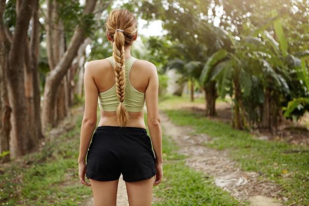 実行する準備ができている木の道に立っている実行中の服を着て女性のジョガーの背面図。屋外でのジョギングトレーニングの準備をする長い三つ編みを持つ若い女性ランナーを決定しました。