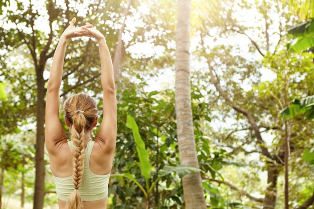 朝のワークアウトセッションの前に公園でウォーミングアップしながら彼女の腕を上げる、美しい運動体と三つ編みの筋肉を伸ばして女性ランナーの背面図。