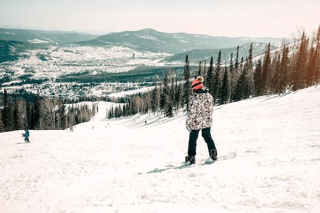 여성 스노보더 스키와 산 풍경을 즐기는 뒷모습 - 아름다운 전망을 갖춘 스노보드 개념