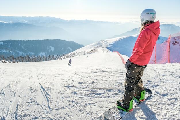 スノーボードと一緒に立って山の風景を楽しんでいる女性のスノーボーダーの背面図。スノーボードのコンセプト