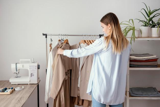 ハンガーで衣服をチェックする女性の仕立て屋の背面図