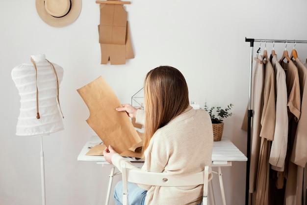 手にパターンを持つ女性の仕立て屋の背面図