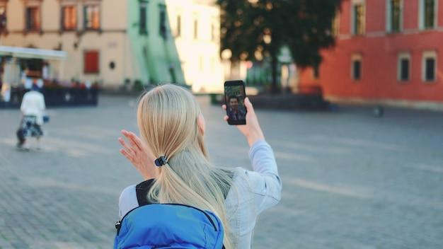 Вид сзади туристки, делающей видеозвонок на смартфоне со своим другом из другого места