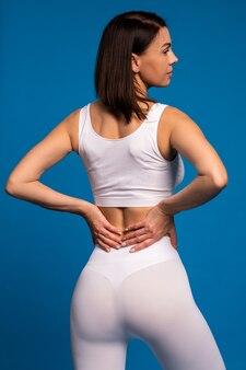 Вид сзади подтянутой женщины в белой спортивной одежде на синей стене