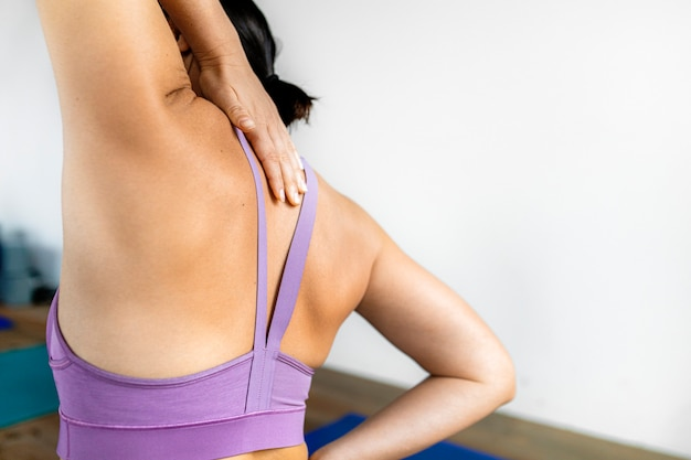 彼女の背中に到達するフィットネス女性の背面図