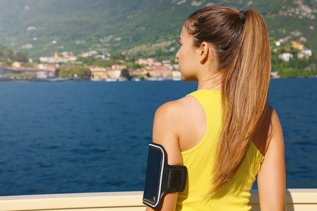 湖での毎日のトレーニングの準備ができて腕章で空白の画面の携帯電話を持つフィットネス女性の背面図。